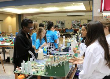 Students showing their Future City model to other students